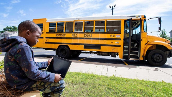 Brayson Lockwood, a student at E.D. Nixon Elementary School, logs onto the internet as a Montgomery Public School bus parks in the lot of the Cleveland Avenue YMCA. The YMCA is one of six locations where internet buses are set up at throughout the county.