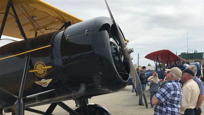 Spectators admire a vintage biplane Wednesday at Benton Airpark in Redding.