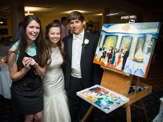 Artist Meredith Piper shares a moment with Caroline and Logan Calhoun as they check out the painting Piper did of their wedding reception.