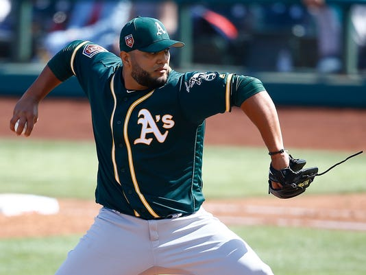 FILE - In this Feb. 27, 2018, file photo, Oakland Athletics relief pitcher Yusmeiro Petit throws a pitch against the Cleveland Indians during the third inning of a spring training baseball game, in Goodyear, Ariz. Petit will be a key bullpen stabilizer for manager bob Melvin, who feels comfortable using the versatile right-hander in several roles _ including starting and long relief.  (AP Photo/Ross D. Franklin, File)