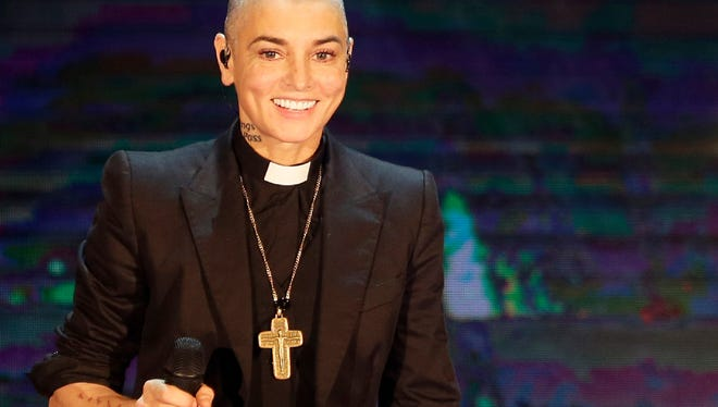 """This is Oct. 5, 2014, file photo of Irish singer Sinead O'Connor performs during the Italian State RAI TV program """"Che Tempo che Fa"""", in Milan, Italy. O'Connor emotionally pleaded for help and opened up about her struggles with mental illness in a rambling Facebook video posted on Aug. 3, 2017. A follow-up Facebook said to be made on O'Connor's behalf late Monday said the singer was OK."""