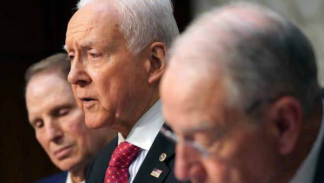 Sen. Orrin Harch, R-Utah, center, discusses the Senate tax overhaul bill.