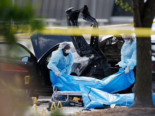 Personnel remove the bodies of two gunmen in Garland,