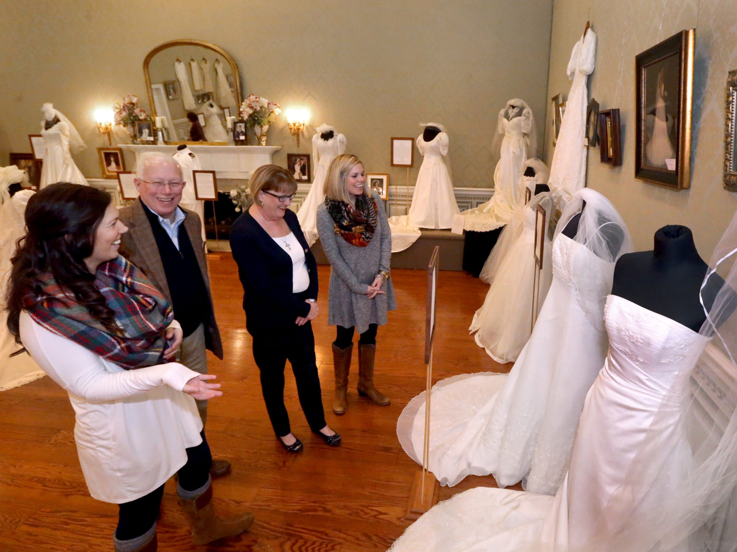 Admiring the 'Wedding Dresses Through the Decades' exhibit gowns are, from left, Brittany Crocker Jackson, her father Mark Crocker and mother Debbie Crocker, and sister Rachel Crocker Pepper.