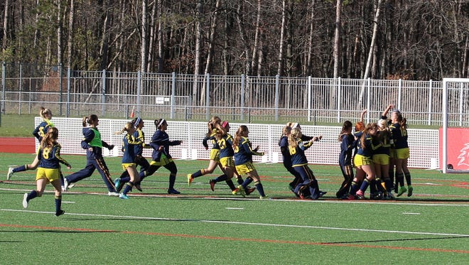 Spencerport girls soccer players sprint onto the field to celebrate Sunday's 2-1 win in the Class  A state championship match.