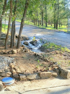 Water gushes out of one of the main line breaks on High Loop Road in Ruidoso.