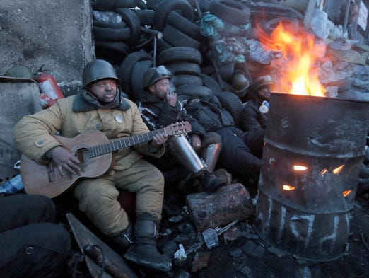 Anti-government activists entertain themselves next to a fire at a barricade in central Kiev, Ukraine, on Jan. 31.