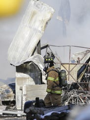 A firefighter walks by remains of a garage after it