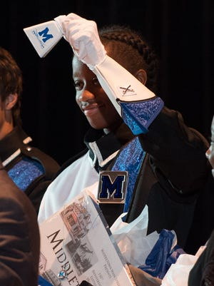 Drum major, Alexa Freeman, a sophomore at Middletown High School, holds up a cow bell which was one of the gifts given to the Deputy Lieutenant of Greater London, Roger Bramble, esq., at the event to officially invite them to perform at the 2018 London New Year's Day Parade.