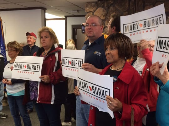 Supporters of gubernatorial candidate Mary Burke hold signs during a Burke campaign stop at headquarters of the Democratic Party of Brown County on Saturday.