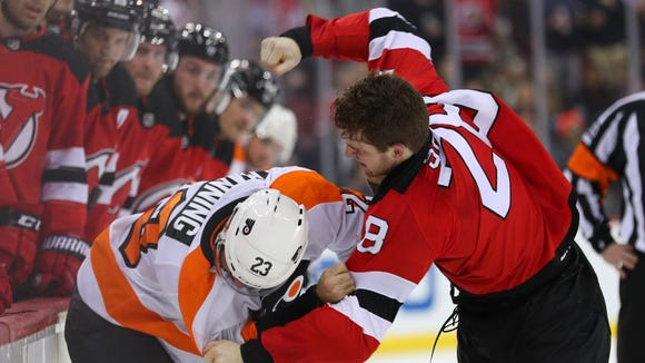 New Jersey Devils defenseman Damon Severson (28) and Philadelphia Flyers defenseman Brandon Manning (23) fight during the first period at Prudential Center.