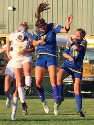 Marian's Morgan Cochran (20) and DeWitt's Kendra Brown (6) engage in some heady work in Wednesday's D-2 state semifinal game played in Novi.