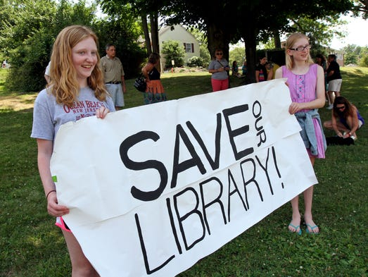 Gwen Kinder, left, and Danae Churchill, hold a Save Our Library sign, outside the Watchung Municipal building. The Friends of Watchung Library deliver a petition in support of a new library building, to Watchung Mayor Stephen Spote, at the Watchung Municipal building, July 11 2014. Watchung NJ. photo by Kathy Johnson BRI 0712 Watchung Library petition