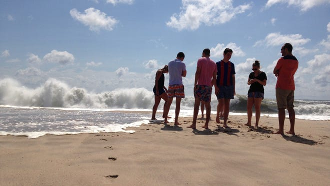Beachgoers stand at the edge of the water, Sunday, Sept. 4, 2016, in Bridgehampton, N.Y., on the southeastern shore of Long Island, where the effects of storm system Hermine could be seen in the rough surf and a ban on swimming. Hermine spun away from the U.S. East Coast on Sunday, removing the threat of heavy rain but maintaining enough power to churn dangerous waves and currents and keep beaches off-limits to disappointed swimmers and surfers during the holiday weekend.