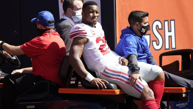 New York Giants running back Saquon Barkley (26) is carted to the locker room after being injured during the first half Sunday against the Chicago Bears.