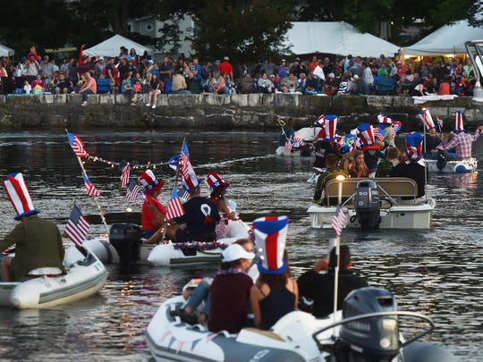 Patriotically decorated vessels head onto the water in the harbor off Clark Park for the Venetian Dinghy Parade at last year's Summer Fest celebration for the Fourth of July in Fish Creek.