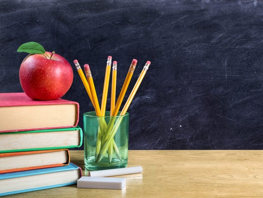 apple on books with pencils and empty blackboard