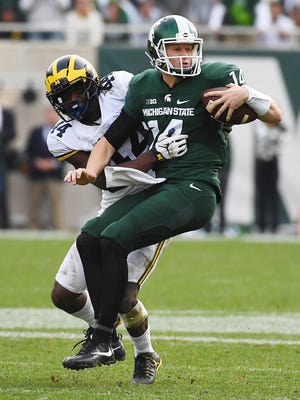 Michigan State Spartans quarterback Brian Lewerke (14) is tackled by Michigan Wolverines safety Delano Hill (44) during the second half at Spartan Stadium.
