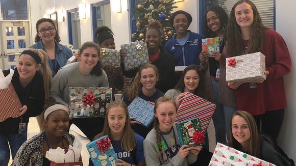 Eastside's girls basketball players display some of the gifts they purchased for two elementary-aged children.