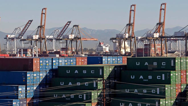 The Ports of Los Angeles and Long Beach, with some cargo loading cranes in the upright and idle position, are seen in this view from the San Pedro area of Los Angeles on Thursday. The ports were closed to ships  Thursday as part of a labor dispute between  employers and dock workers.