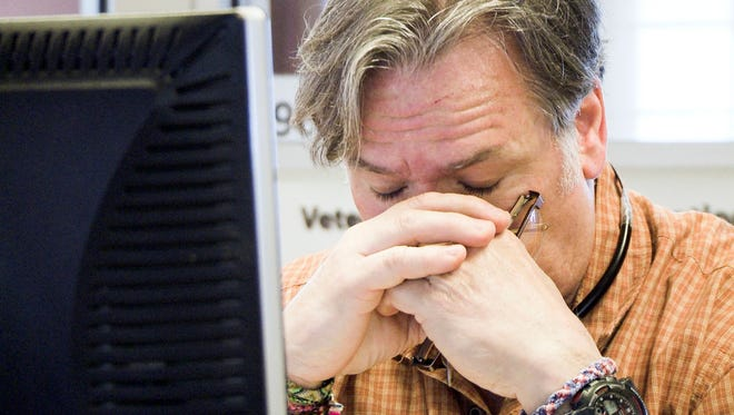 "An unidentified staffer at the Veterans Crisis Line in Canandaigua, N.Y., reacts to a caller during the 2013 filming of the HBO documentary ""Crisis Hotline: Veterans Press 1."""
