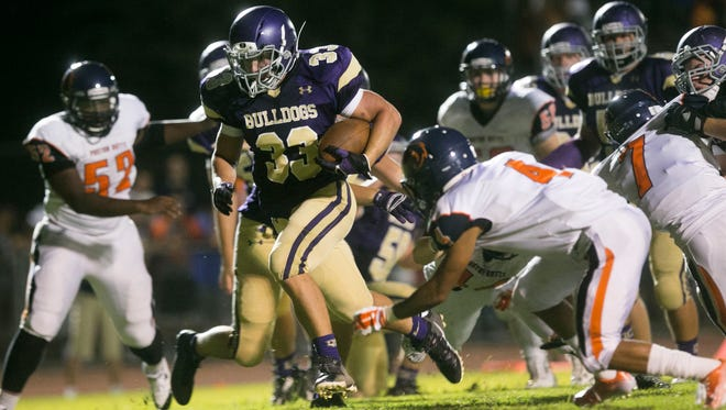 Queen Creek running back Weston Barlow breaks through the Poston Butte defense on his way to scoring a rushing touchdown on Friday, Aug. 22, 2014.