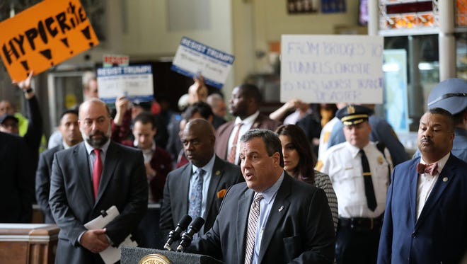 Protesters affiliated with New Jersey Working Families, a political advocacy organization, hold up a signs behind Gov. Chris Christie as he speaks Wednesday as a news conference at Newark Penn Station. Protesters said, among other things, they objected to Christie's decision to cancel the Access to the Region's Core infrastructure project in 2010.