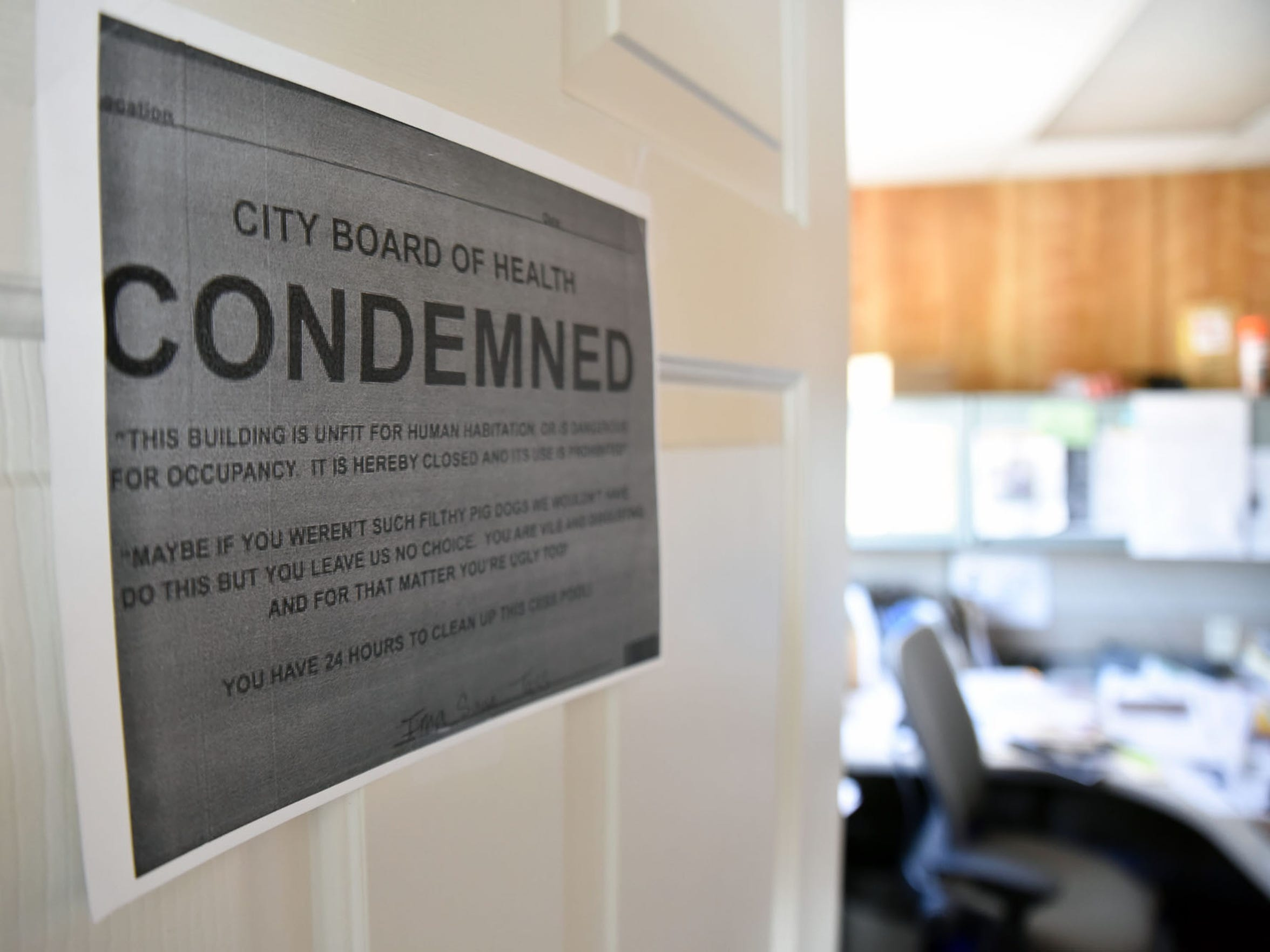 Cindi Gil-Blanco works out of her small office behind the Waste Management transfer station. A co-worker put a city board of health condemned sign on her door.