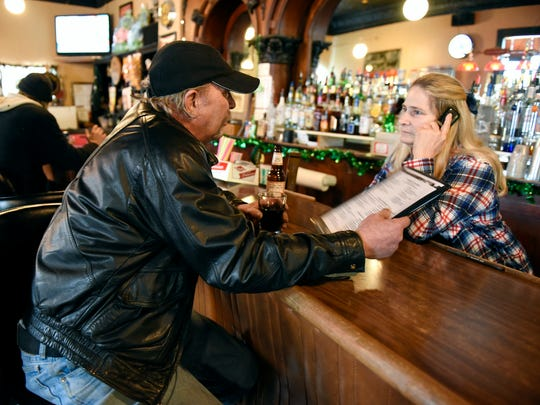 Sandy Brutger, owner of The Lion's Den, orders lunch for Gary Harren, St. Anna, from the Cabin Cafe across the street Friday, March 4, in Avon.