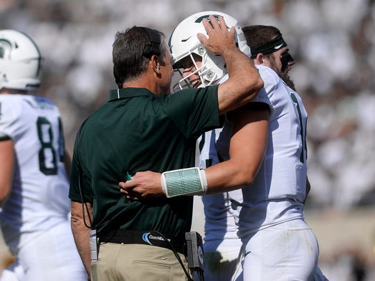 Michigan State's Brian Lewerke, right, celebrates his