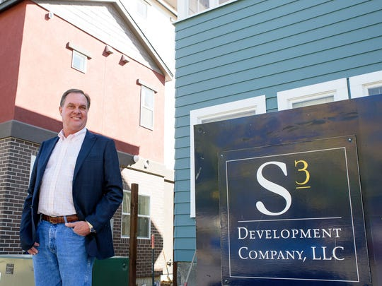 Blake Smith, owner of S3 Development, poses in front of one of the new Midtown Lofts on Stewart and Sinclair streets.