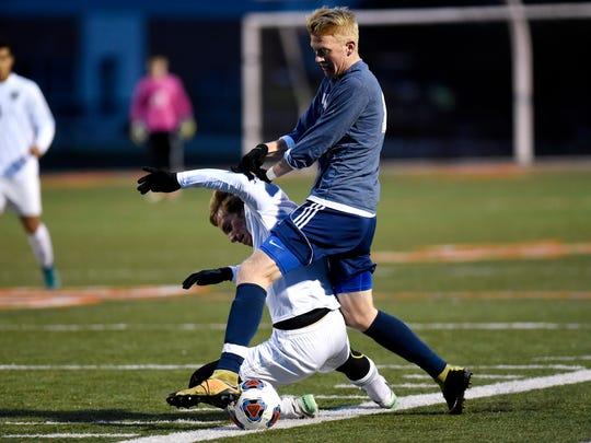 East Lansing's Petrus Martens, right, collides with
