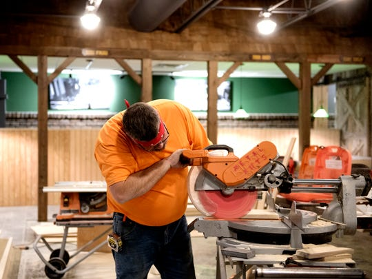 A contractor cuts wood while flood renovations are