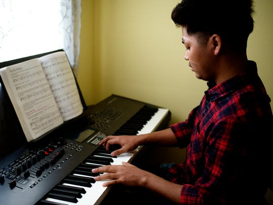Tung Sian Hau plays a piece of music on a piano that his father purchased for him on Wednesday, May 16, 2018, in his new Lansing home after he was reunited with his Myanmar refugee parents after a decade apart.