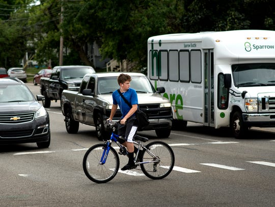 A boy crosses Pennsylvania Avenue at Shiawassee Street on Thursday, June 21 in Lansing near where the city plans to create an access point for a proposed east side connector bike and pedestrian route.
