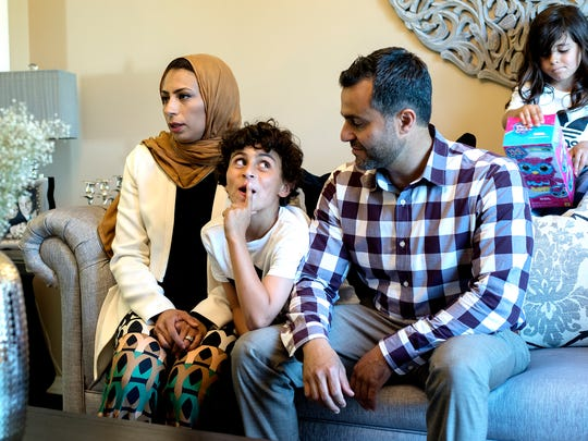 Dr. Ahmed El-Sanhouri, a retina specialist, right, and his wife Dr. Aya Zaky, a dentist, left, speak about their upcoming trip to provide care to Syrian refugees living in Jordan as two of their three children Yusef, 9, center, and Noor, 5, right, listen on Friday, June 29, 2018, at their home in East Lansing.