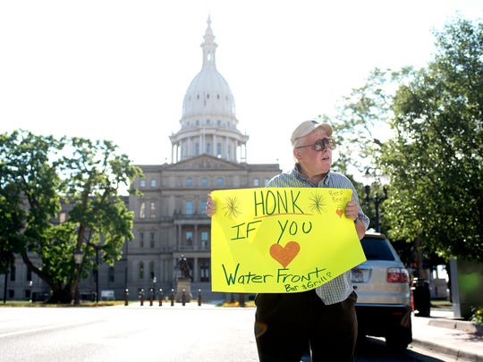 Dan Kovacs holds a sign while protesting the possible closure of the Lansing City Market on Monday, July 9, 2018, outside Lansing City Hall. The rally was organized by Patrice Drainville, vice president of operations for the Waterfront Bar and Grill, a City Market tenant that is concerned about the end of its lease.