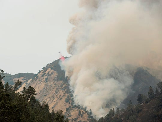 A helicopter drops retardant on the Ferguson fire on