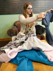 "Anna Budelman sorts through clothes Tuesday, Feb. 6, 2018, in the Todd Wehr Alumni Center, that was hung as part of an exhibit titled ""What Were You Wearing."" Displayed were examples of clothing similar to what sexual assault survivors were wearing at the time of their attack."