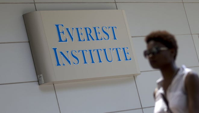 A woman walks past an Everest Institute sign in an office building in Silver Spring, Md., on July 8, 2014.