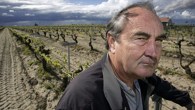 In this April 10, 2006, file photo raisin farmer Marvin Horne stands in a field of grapevines planted in 1918 next to his home in Kerman, Calif.