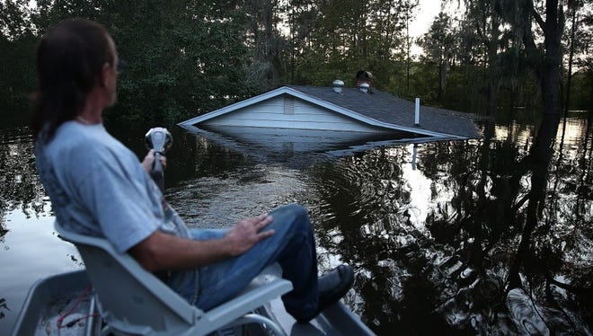 Buddy Benford pilots his boat past a home in Andrews, S.C., nearly submerged by water coming from the breached dams upstream.
