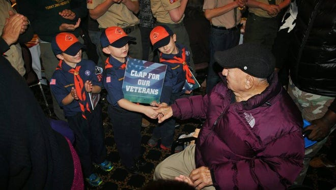 A veteran shanks hands with a Cub Scout at one of the past Veterans Thanksgiving Dinners.