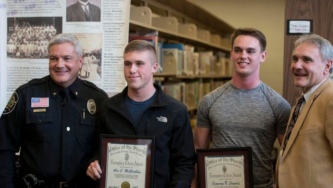 From left: Buncombe County Sheriff Van Duncan, Erwin students Alex McGlothlin and Cameron Connors, and district superintendent Tony Baldwin pose for a picture after McGlothlin and Connors were honored March 8 in Erwin High School's media center.
