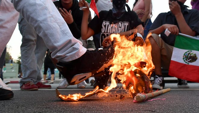 A Trump hat burns during a protest near where Republican presidential candidate Donald Trump held a rally in San Jose, California on June 02, 2016. Protesters attacked trump supporters as they left the rally, burned an american flag, trump paraphernalia and scuffled with police and each other.