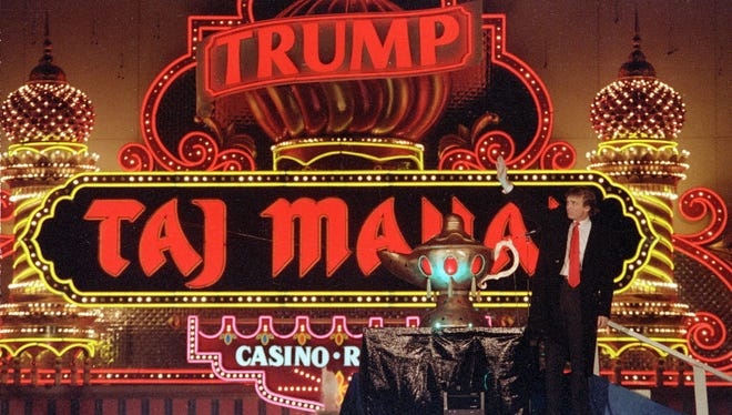 Donald Trump stands next to a genie lamp as the lights of his Trump Taj Mahal Casino Resort light up the evening sky marking the grand opening of the venture in Atlantic City, N.J., on April 5, 1990.