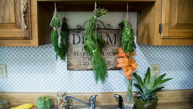 Katie Sims hangs herbs, spices and other plants that she grows in her kitchen. She also dehydrates her herbs and uses them as decorations.