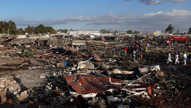 Firefighters and rescue workers walk through the scorched ground of Mexico's best-known fireworks market after an explosion explosion ripped through it, in Tultepec, Mexico, Tuesday, Dec. 20, 2016.