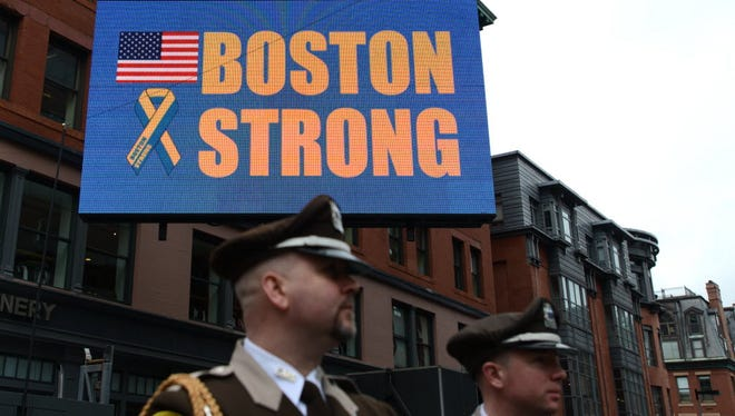 Boston Honor Guard members stand near a BostonStrong digital sign on Exeter Street near the finish line of the Boston Marathon in this 2015 file photo.