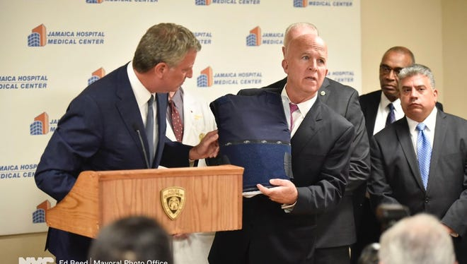 New York City Mayor Bill de Blasio (left) and Police Commissioner James O'Neill (right) display the bulletproof vest that saved Officer Hart Nguyen's life.
